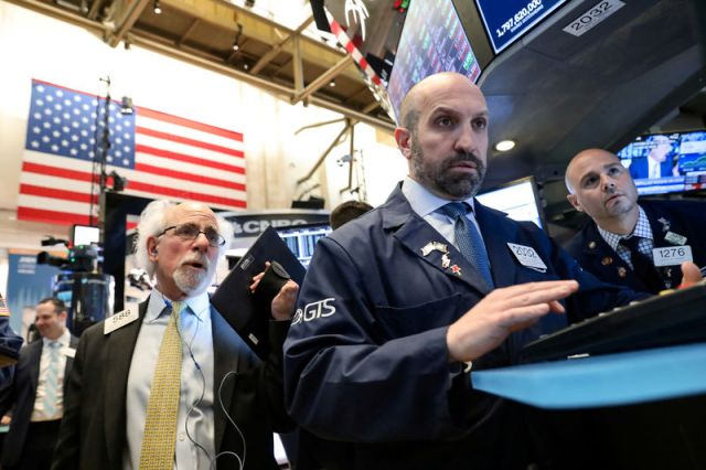 © Reuters. FILE PHOTO: Traders work on the floor at the NYSE in New York