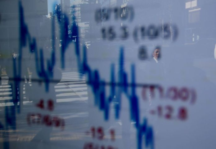 © Reuters. FILE PHOTO: A man is reflected on an electronic board showing a graph analyzing recent change of Nikkei stock index outside a brokerage in Tokyo