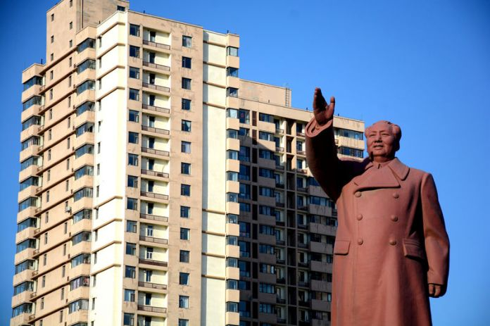 © Reuters. FILE PHOTO: Statue of former Chinese chairman Mao Zedong is seen in front of a residential building in Dandong New Zone