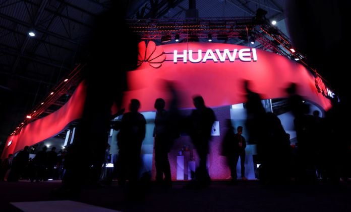 © Reuters. FILE PHOTO: Visitors walk past Huawei's booth during Mobile World Congress in Barcelona