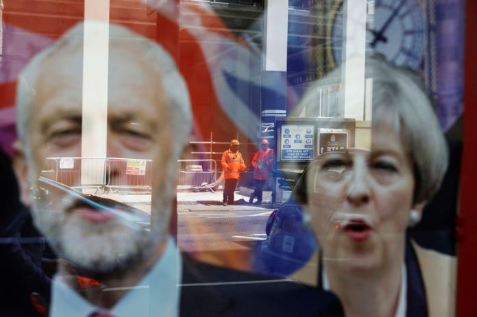 © Reuters. Wokers are reflected in the window of a betting shop with a display inviting customers to place bets on tbe result of the general election with images of Britain's Prime Minister Theresa May and opposition Labour Party leader Jeremy Corbyn, in London