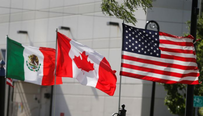 © Reuters. Flags of the U.S., Canada and Mexico fly next to each other in Detroit, Michigan