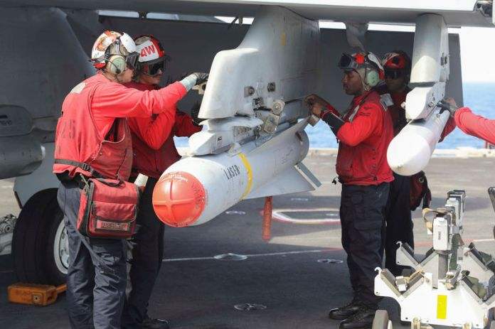© -. FILE PHOTO: Flight dec crew remove ordnance from an F/A-18E Super Hornet on the flight deck of the aircraft carrier USS Abraham Lincoln (CVN 72), in Arabian Sea