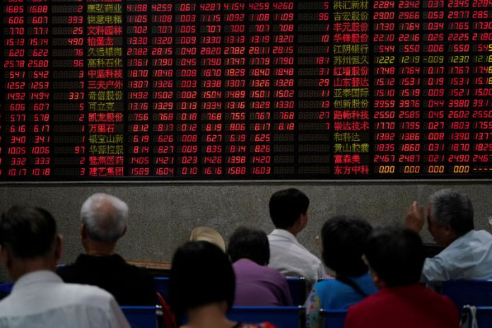 © -. Investors look at an electronic board showing stock information at a brokerage house in Shanghai