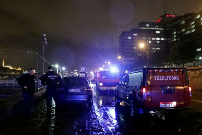 © -. Police and fire brigade vehicles are seen on the Danube bank after tourist boat capsized on the riverin Budapest