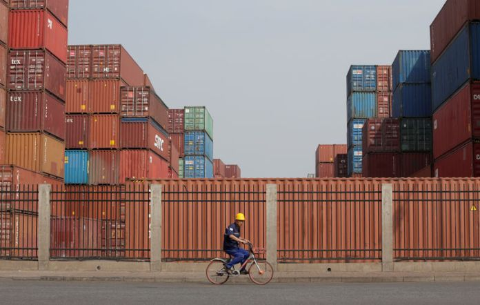 © -. A worker cycles past containers outside a logistics center near Tianjin Port