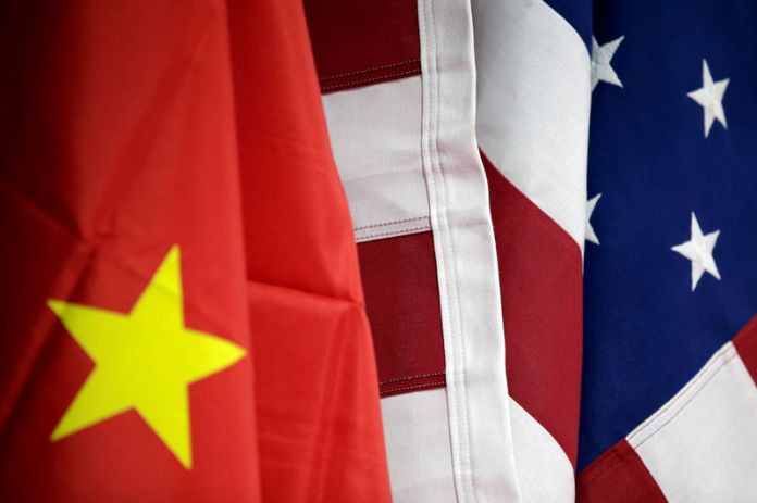 © -. FILE PHOTO: Flags of U.S. and China are displayed at AICC's booth during China International Fair for Trade in Services in Beijing