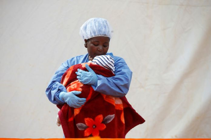 © -. FILE PHOTO: Rachel Kahindo, an Ebola survivor working as a caregiver to babies who are confirmed Ebola cases, holds an infant outside the red zone at the Ebola treatment centre in Butembo