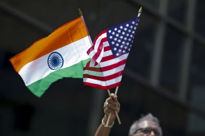 © -. Man holds the flags while people take part in the 35th India Day Parade in New York