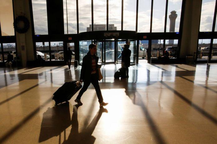 © -. FILE PHOTO: Travelers make their way through Newark Liberty International Airport in Newark, New Jersey