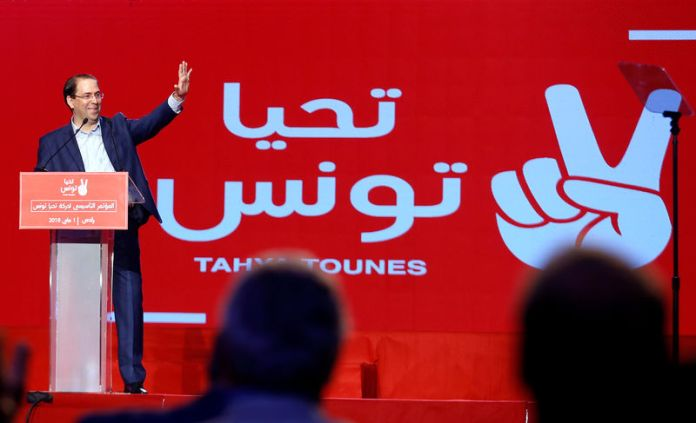 © -. Tunisian Prime Minister Youssef Chahed waves during a meeting of the 'Long Live Tunisia' party in Tunis