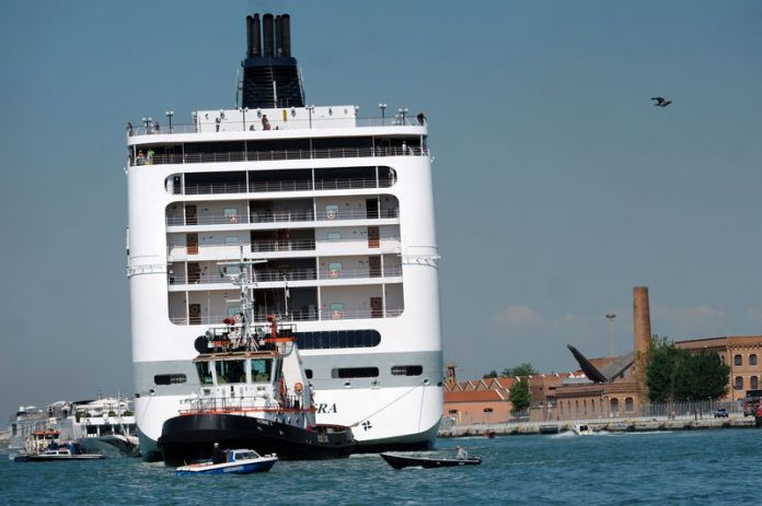 © -. The cruise ship MSC Opera loses control and crashes against a smaller tourist boat at the San Basilio dock in Venice