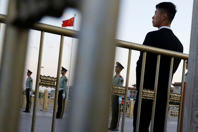 © -. Security officers keep watch at Tiananmen Square in Beijing