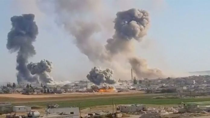 © -. Plumes of smoke rise from a location, said to be Khan al Subul, Idlib province, Syria, targeted in a strike