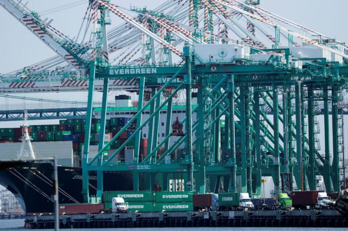 © -. Trucks offload containers from ship at the port of Los Angeles in Los Angeles, California
