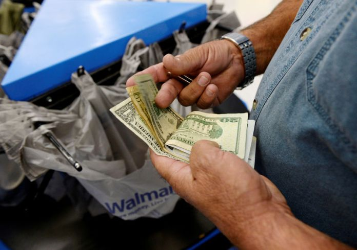 © -. FILE PHOTO: FILE PHOTO: A customer counts his cash at the checkout lane of a Walmart store in the Porter Ranch section of Los Angeles
