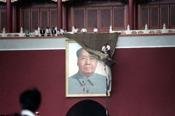 © -. FILE PHOTO: Workmen try to drape the portrait of Mao Zedong in Tiananmen Square in Beijing