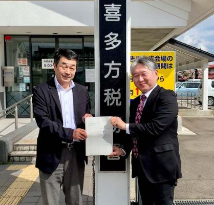 喜多方税務署前で免許通知書を手に記念撮影をする副社長の阿部と専務の磯部