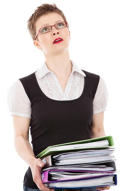 Mujer con archivadores y cara de preocupación.