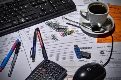 Escritorio con calculadora, teclado café, bolígrafos, facturas.
