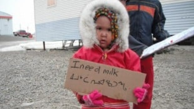 A child holds a sign at a protest against high food prices in Nunavut in June 2012. A new strategy from the Nunavut Food Security Coalition says helping people hunt and share more caribou, seal and other traditional foods could help tackle the 'food security crisis' in the territory.