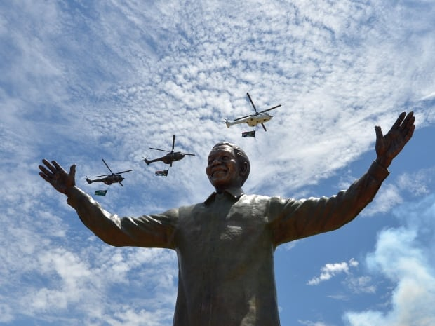Helicopters carrying the South African flag fly over a nine-metre bronze statue of former South African president Nelson Mandela that was unveiled on Dec. 16 in Pretoria, the country's administrative capital. On a public holiday dedicated to reconciliation, South Africans started coming to terms with the loss of Mandela, a day after he was buried at the end of a life struggle for freedom and equality. Mandela was inaugurated as South Africa's first black president in 1994.