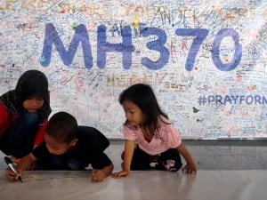 Children in Kuala Lumpur write messages on a 60-metre long banner filled with well wishes for all involved with missing Malaysia Airlines Flight MH370.