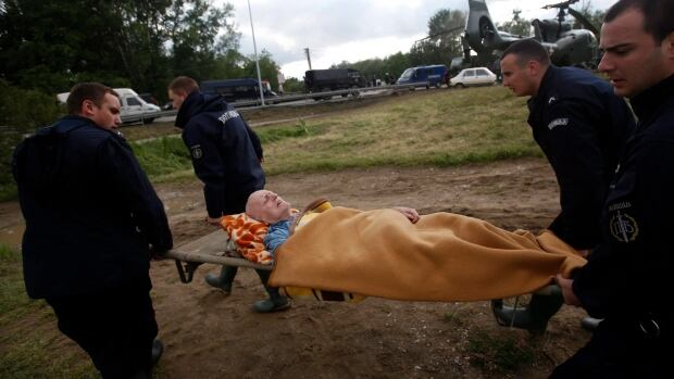Serbian police officers carry a man from a military helicopter during flood evacuation from Obrenovac, some 30 kilometers (18 miles) southwest of Belgrade Serbia, Saturday, May 17, 2014.