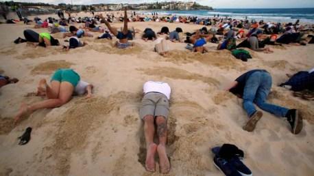 Un grupo de unos 400 manifestantes participan en una protesta el cambio climático por enterrar sus cabezas en la arena en la playa de Bondi de Sydney el jueves.  Se llevó a cabo antes de la cumbre del G-20 del sábado en Brisbane.