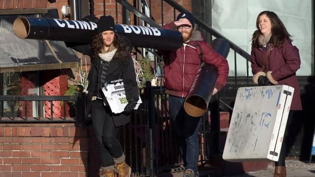 Members of Stop Energy East Halifax head to a protest outside the library in Halifax on Monday.