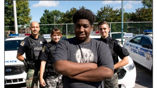 Malyk Bonnet, 17, poses with Laval police officers after helping rescue a kidnapping victim.