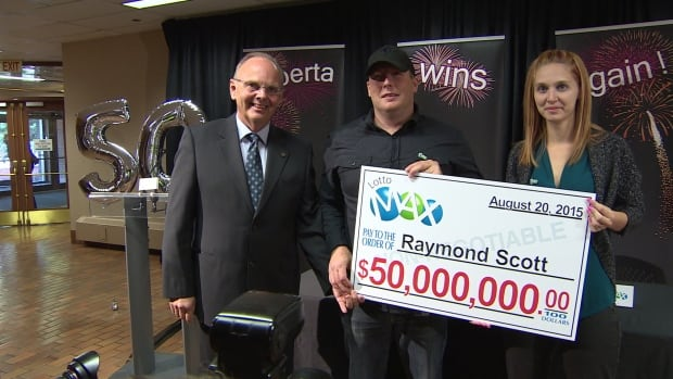 Raymond and Sheena Scott are presented with a whopping big check by Bill Robinson, president of the Alberta Gaming & Liquor Commission.