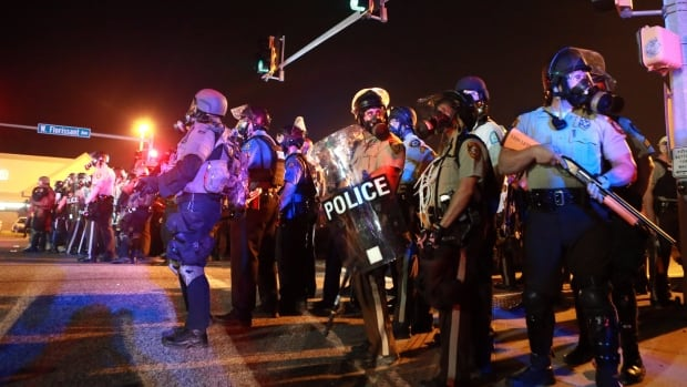 Police from various departments stand guard on Aug. 18, 2014, in Ferguson, Mo., just days after a grand jury decision not to indict the white police officer who had shot and killed an 18-year-old African-American sparked protests.