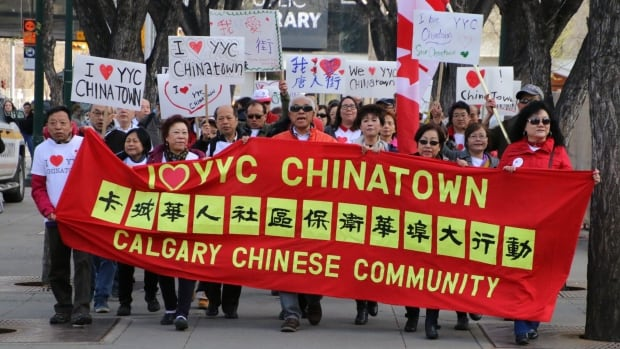 Opponents of a 27-storey development proposed for Calgary's downtown Chinatown area march to a rally outside city hall.