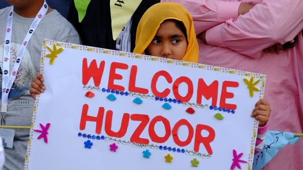 A young Ahmadiyya Muslim girl welcomes the caliph, Mirza Masroor Ahmad, with a sign that means 'Welcome, present one.' The spiritual leader arrived in Toronto on Monday afternoon.