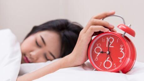 Sleeping woman with clock