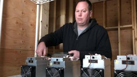 Dan Ingram sets up some of his new bitcoin mining machines in a warehouse space he's renting in B.C.'s lower mainland.