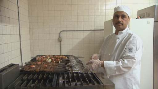 Al Hilal works the grill in his shop's kitchen. (David Laughlin/CBC)