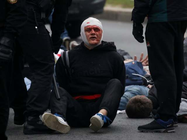 An injured demonstrator sits on the ground after being detained by officers during an opposition rally in Minsk, Belarus, on Oct. 11, 2020.