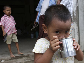 A homeless Burmese boy drinks clean water at a monastery for a temporary shelter on the outskirts of Yangon, Myanmar.