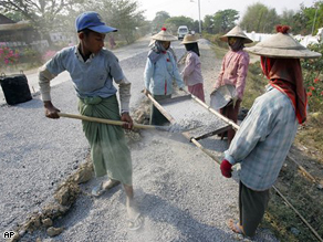 A road construction crew in Myanmar adds new surface to a highway north of Yangoon.