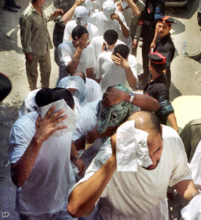 52 Egyptian men accused of allegedly engaging in homosexual sex during a party cover their faces as they arrive to the court for the second session of their case in Cairo, August 2001.