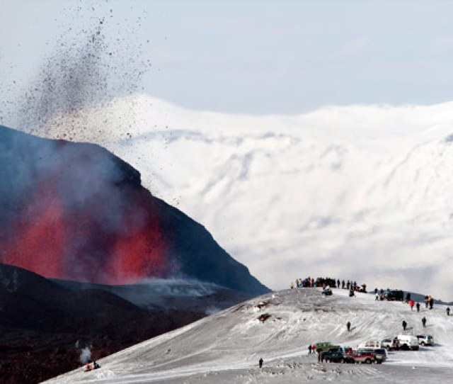 Tourists Gather To Watch Lava Spurt Out Of The Site Of A Volcanic Eruption At The