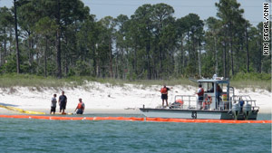 A containment boom is laid at Pensacola beach to protect the shore from the approaching oil.- from CNN