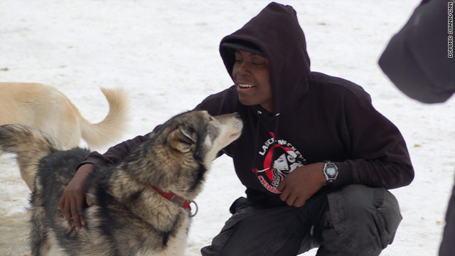 Rookie musher Newton Marshall of Jamaica bonds with borrowed lead dog Larry in Anchorage, Alaska.
