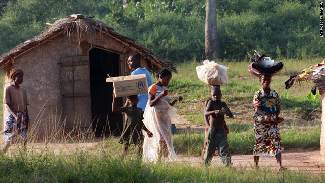 Ivorian refugees walk in the village of Loguatuo on December 14. About 4000 people have flooded into Liberia since early this month, according to the UN refugee agency.