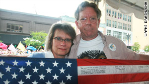 Lori and Jeff Wilfahrt attend their first gay pride parade. They hold a flag signed by their son's comrades.