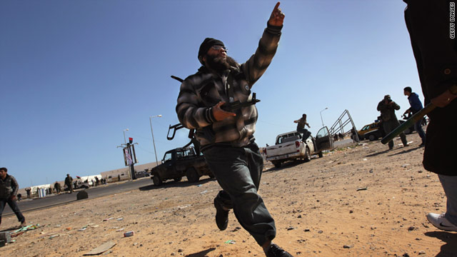 An opposition fighter runs for cover during a government airstrike in the area of Ras Lanuf, Libya, on Monday .