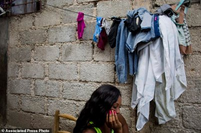 Lovely Harasme 26, sits in front of her mother's house in Port-au-Prince, Haiti. She says she was one of several women who worked as prostitutes for Sri Lankan peacekeepers with the U.N.