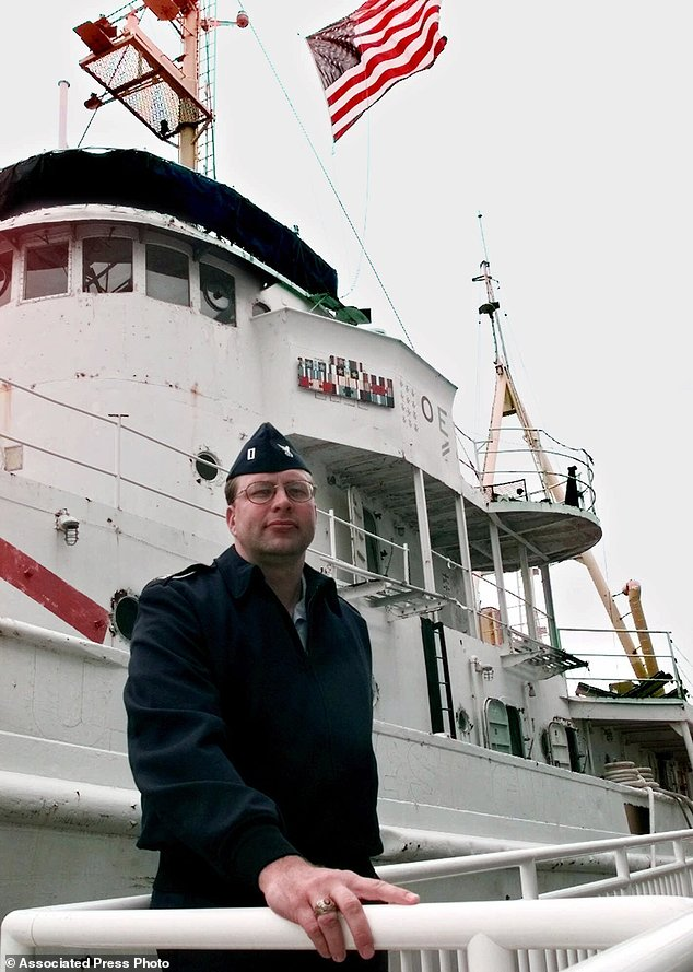U.S. Coast Guard Lt. William Moeller of Northford, Conn., poses for a photo in front of the USS Tamaroa. Moeller was aboard the Tamaroa during the 1991 rescue of five Air National Guardsmen who ditched their helicopter as they were trying to rescue the crew of a fishing boat during a fierce storm.